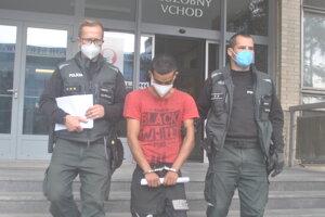 Policajti odvádzajú obvineného do väznice.