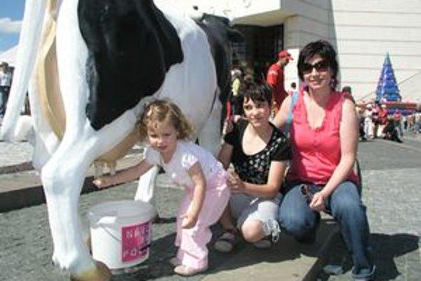 Podojiť umelú kravu sa na Kraváli pokúšala aj 2-ročná Lea Maťavková. Vedľa nej sestra Klára s maminou Andreou.