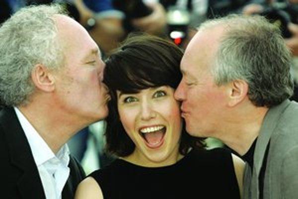 Belgickí bratia Jean-Pierre Dardenne (vľavo) a Luc Dardenne bozkávajú tureckú herečku Artu Dosbrosi, predstaviteľku hlavnej úlohy v ich filme Lornino mlčanie.