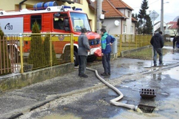 Vodu z pivníc pomáhajú odčerpávať hasiči.
