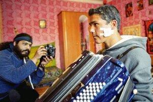 Mário Bihári fotografuje mladého rómskeho hudobníka v Jarovniciach.