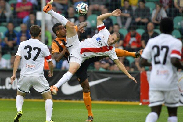 Trenčan Milan Rundič (uprostred v bielom) a hráč hostí Tom Huddlestone z Hull City.