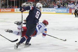 Ruský hokejista Artemij Panarin padá na ľad po súboji s Jackom Eichelom.