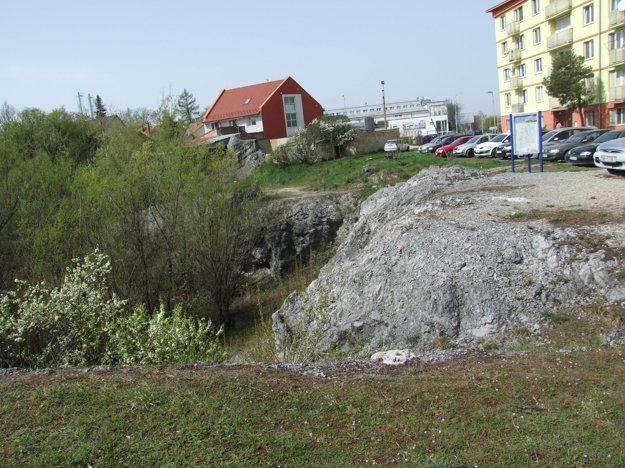 Nad baňou sú rodinné domy, v dolnej časti stojí panelák.