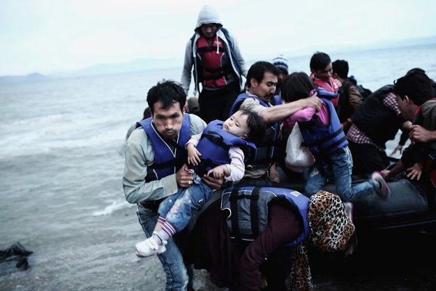 Pri hľadaní európskeho sna. Afganský utečenec nesie svoje dieťa po vylodení na pláži na gréckom ostrove Kos.