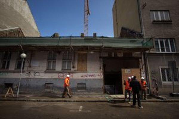 Na dome už rozobrali strechu, nákladné autá sa dnu dostávajú dierou v stene.