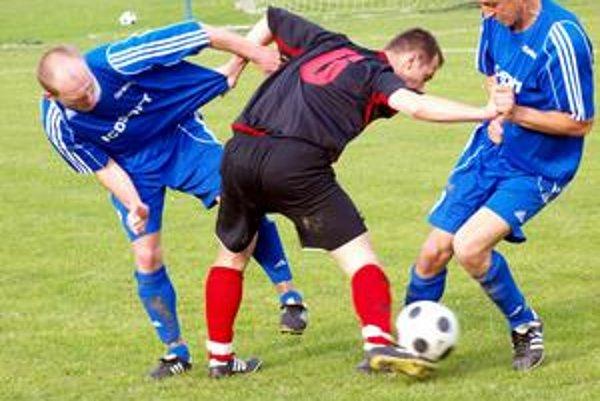 Hráči Čunova Ján Lečko (vľavo) a Kamil Kovasich sa snažia zastaviť hráča Rece Petra Bozsika. Zo zápasu 19. kola III. futbalovej ligy ŠK Čunovo – ŠK Reca 0:2.