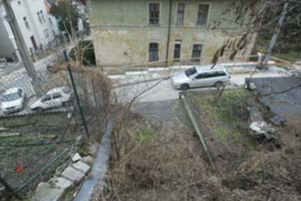 Z Donovalovej ulice steká voda po strechách garáží na Vlčkovu. Zosuvu podmáčaného svahu na dom má zabrániť oporný múr. Zatiaľ je dokončený len čiastočne.