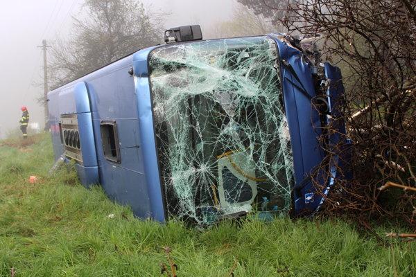 Autobus skončil prevrátený mimo cesty.