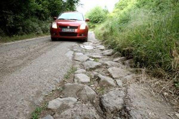 Cesta sa rozsýpa po oboch okrajoch.