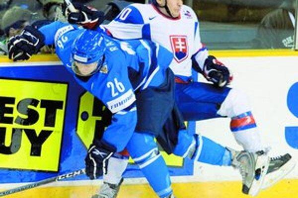 Útočník Slovenska Martin Uhnák (v bielom) v tvrdom súboji pri mantineli s fínskym hráčom Joonasom Raskom. V poslednom zápase základnej B-skupiny juniorských majstrovstiev sveta v Ottawe zvíťazili mladí Slováci 3:2 po samostatných nájazdoch a postúpili do