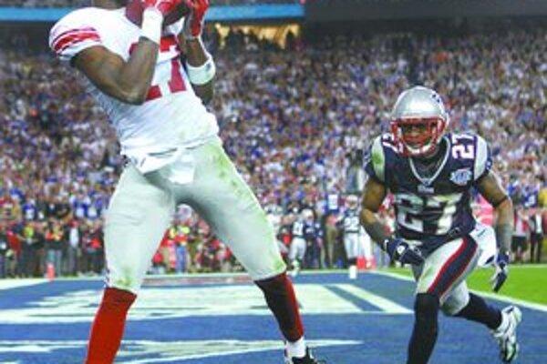 Plaxico Burress (vľavo) z New York Giants prijíma prihrávku na víťazný touchdown. Vpravo je obranca New England Patriots Ellis Hobbs vo finále amerického futbalu Super Bowl Giants - Patriots 17:14.