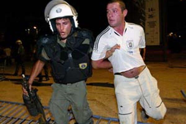 Policajt zasahuje proti fanúšikovi PAOK Solún.