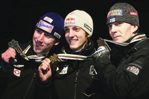 Rakúšan Gregor Schlierenzauer (18, v strede) sa stal v sobotu v Oberstdorfe majstrom sveta v letoch na lyžiach. S krajanom Martinom Kochom (vľavo) sa tešili včera aj z prvenstva v súťaži družstiev. Vpravo je bronzový tridsiatnik Janne Ahonen z Fínska.