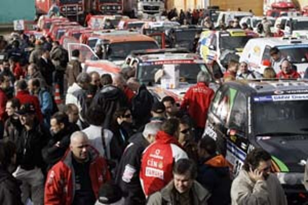 Šéf Rely Dakar Etienne Lavigne (na snímke dolu) smúti po správe, ktorú musel oznámiť účastníkom podujatia.  Na snímke hore pretekári pri svojich vozidlách rozoberajú nečakanú zvesť.