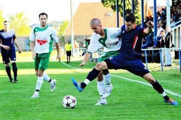 Futbalisti Kozároviec ( v modrom) dosiahli svojim tretím miestom historický úspech. Záber je z ich zápasu proti Okoličnej.
