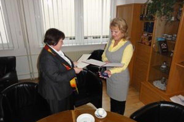 Ľ. Benkovičová (vľavo) venovala M. Jeseničovej pamätnú medailu, ďakovný list a osobitnú edíciu známok.