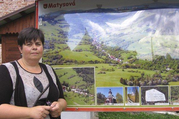 Starostka obce Matysová Iveta Kundrátová pred tabuľou dediny s vyznačenými turistickými chodníkmi.