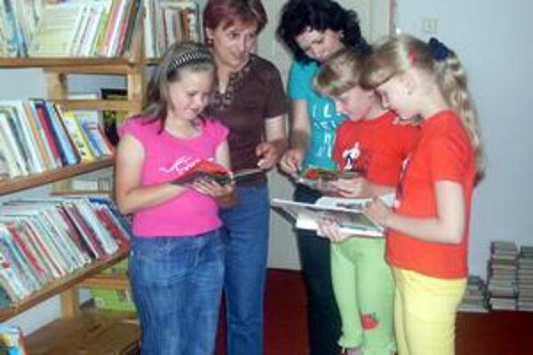 V knižnici. Deti ukazujú, čo ich najviac zaujíma.