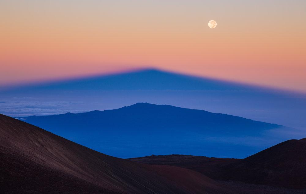 Tieň najvyššieho Havajskeého vrcholu Manua Kea sa premieta nad sopkou Hualalai vďaka vychádzajúcemu Slnku. FOTO - Sean Goebel