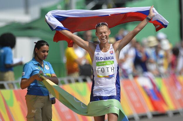 Matej Tóth pretína cieľovú pásku so slovenskou vlajkou v rukách.