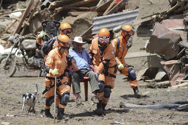 Záchranári vynášajú na stoličke muža, ktorý prežil po zosuve pôdy v Salgare.