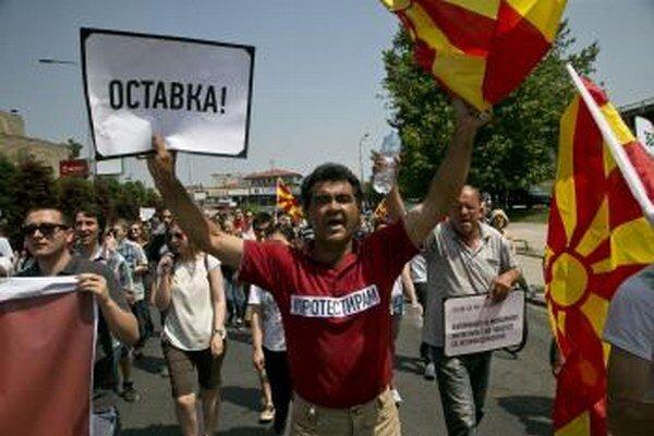"""Demonštrant drží transparent s nápisom """"Demisia"""" počas opozičného zhromaždenia v macedónskej metropole Skopje v nedeľu 17. mája 2015."""