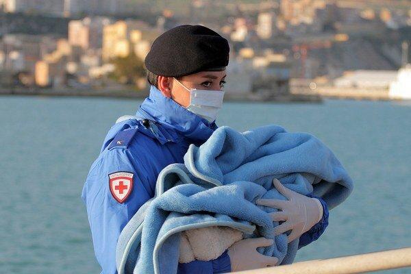 Pracovníčka Červeného kríža nesie bábätko zabalené v deke počas príchodu zachránených afrických imigrantov na lodi do sicílskeho prístavu Porto Empedocle.