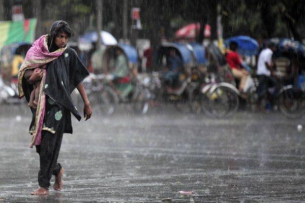 Na snímke chudobná bangladéšska žena nesie v náručí dieťa na križovatke v daždi v Dháke 18. marca 2015.