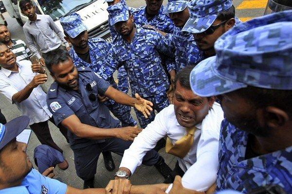 Bývalý maldivský prezident a neskorší vodca maldivskej opozície Muhammad Našíd zápasí s policajtmi, ktorí ho zadržali počas brífingu v Male 23. februára 2015.