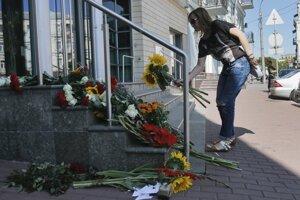 Žena kladie pred holandské veľvyslanectvo v ukrajinskom Kyjeve kvety.