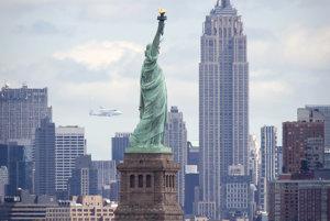 Socha slobody v pozadí s mrakodrapom Empire State Building a lietadlom Boeing 474, ktoré prepravuje raketoplán Enterprise.