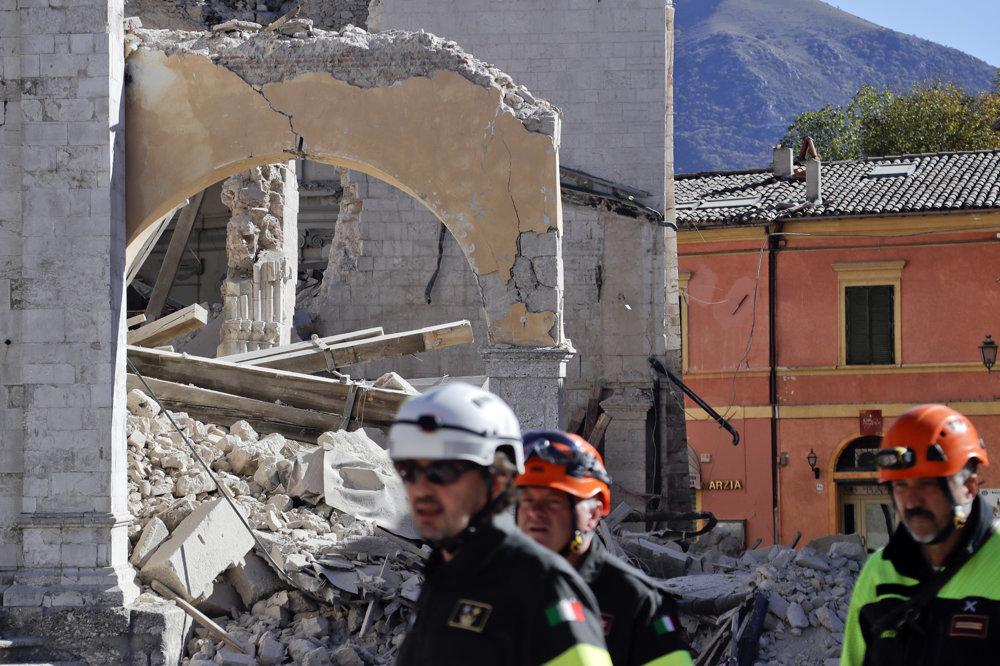 Hasiči pred zničenou bazilikou sv. Benedikta  v stredotalianskom historickom meste Norcia po silnom zemetrasení.