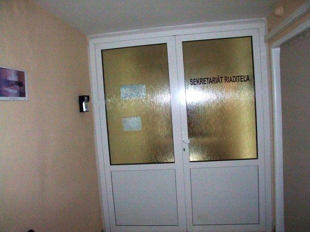 Kancelária riaditeľa sa nachádza za týmito zamknutými dverami, na stene je zvonček.