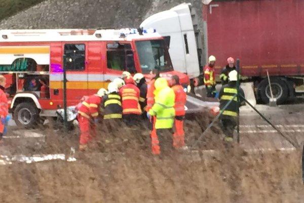 Hasiči a záchranári sa snažia dostať k vodičovi Audi.