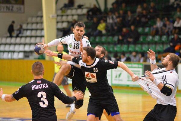 Vo výskoku sloptou Novozámčan Gabriel Vadkerti bránený hráčmi Topoľčian. Vpravo za dres ťahaný Erik Ľoch.