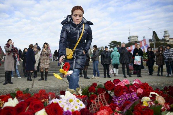 Na snímke žena kladie kvety na mólo počas piety za obeťami tragickej nehody lietadla Tu-154.