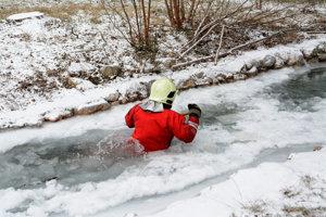 Hasič sa brodí. Snaží sa uvoľniť ľad.