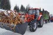 Preprava na štart bola veľkou atrakciou. Traktor odviezol v radlici sánky a vo vlečke pretekárov.