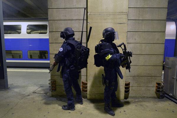 Policajti hliadkujú na stanici v Montparnasse po parížskych útokoch.