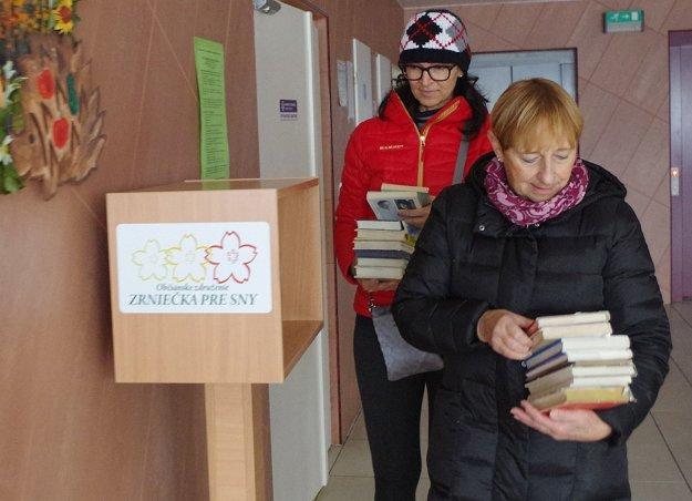 Katarína Beranová a Miriam Kudlová pri napĺňaní knižnej búdky publikáciami.