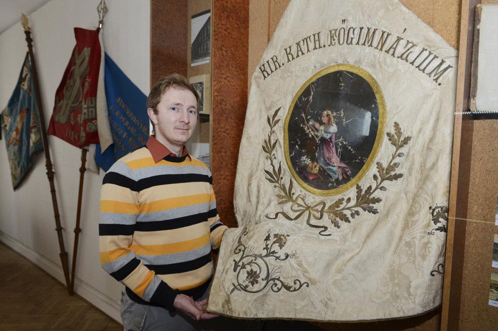 Zástupca riaditeľa múzea historik Jozef Kušnír pri zástave kráľovského katolíckeho hlavného gymnázia.