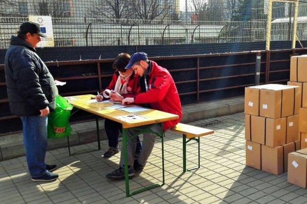 Pracovníci charity rozdali balíky z potravinovou pomocou.