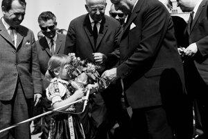Dievčatko dáva kyticu vtedajšiemu prezidentovi Ludvíkovi Svobodovi počas kladenia vencov na Slavíne. Vľavo od Svobodu stoja Gustáv Husák a Vasiľ Biľak.