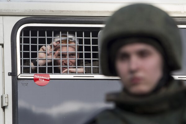 Policajné auto odváža Navaľného z demonštrácie.