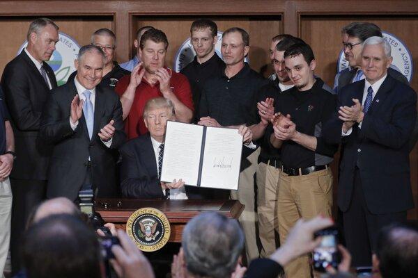 Trump s baníkmi v pozadí pri podpisovaní dekrétu.