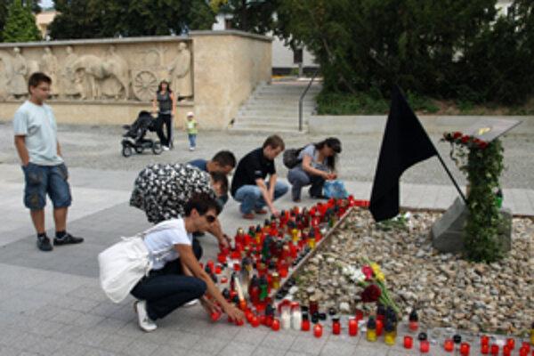 Ľudia zapaľujú sviečky na pietnom mieste v centre mesta.