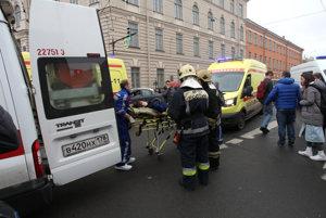Záchranári vynášajú na nosidlách zranenú ženu.