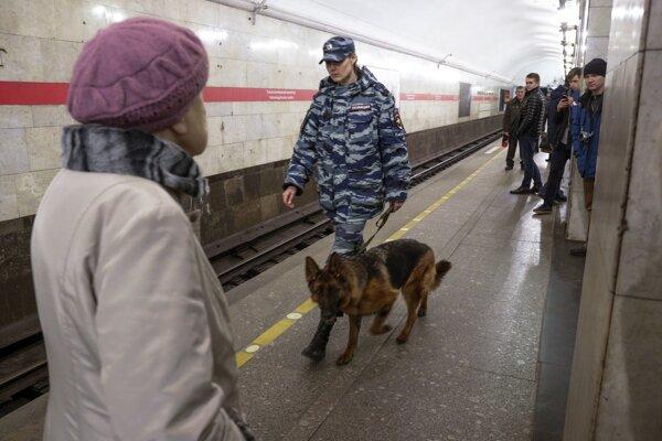 Petrohradská policajtka prehľadáva so služobným psom zastávku metra Technologický inštitút.