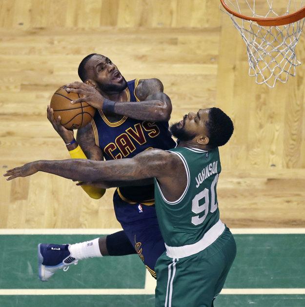 LeBron James (vľavo) z Clevelandu sa prediera do zakončenia cez Amira Johnsona.